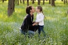 A mamã agachada e toca delicadamente no nariz da filha fotos de stock