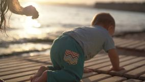 A mamã agrada um bebê pequeno perto do mar no por do sol no movimento lento