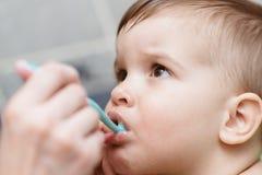 A mamã ajuda seu filho novo a escovar seus dentes fotografia de stock