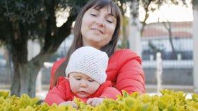 A mamã alegre mantém as folhas verdes tocantes do bebê pela primeira vez video estoque