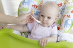 A mamã alimenta o bebê com uma colher imagens de stock