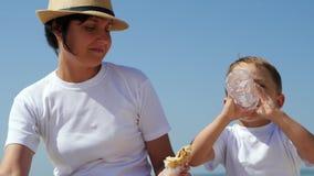 A mamã alimenta sua criança com os Hamburger no litoral arenoso, a criança come um Hamburger e bebe a água de um plástico video estoque