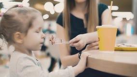 A mamã alimenta uma filha pequena com uma forquilha, eles senta-se em um café vídeos de arquivo