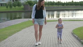 A mamã anda com uma filha pequena no parque vídeos de arquivo