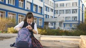A mamã anda sobre e beija meninas adolescentes perto da faculdade A menina do estudante que senta-se no pátio da faculdade e é video estoque