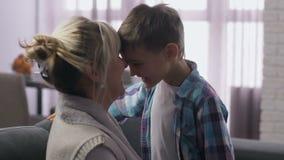 Mamã ascendente próxima com o filho que tem os narizes de fricção do divertimento
