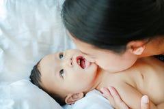 Mamã asiática do close-up que joga e que beija seu pouco bebê na cama imagens de stock royalty free