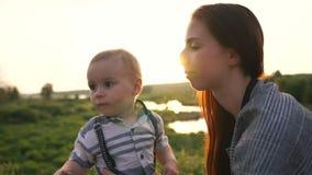 A mamã beija o bebê na esponja, ele estica a seu ar livre no movimento lento video estoque