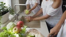A mamã bonita nova e suas duas filhas bonitas lavam junto as maçãs verdes na banca da cozinha que prepara-se a video estoque