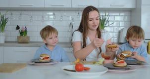 A mamã bonita nova em um vestido branco com duas crianças é de sorriso e comendo hamburgueres frescos em sua cozinha vídeos de arquivo