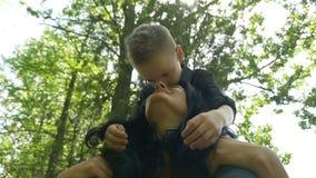 Mamã bonita nova que leva seu filho feliz em seus ombros com as árvores no fundo vídeos de arquivo