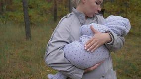 Mamã bonito nova que guarda um bebê no parque video estoque