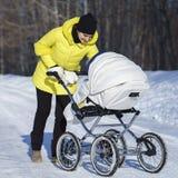 A mamã caucasiano no revestimento amarelo está andando com o transporte de bebê branco na estrada da neve entre a floresta no dia Imagem de Stock Royalty Free