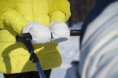 A mamã caucasiano no revestimento amarelo está andando com o transporte de bebê branco na estrada da neve entre a floresta no dia Imagem de Stock