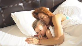 A mamã com bebê do filho acordou na manhã na cama video estoque