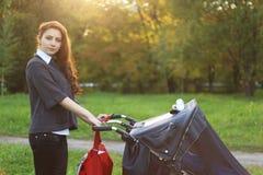A mamã com carrinho de criança anda na aleia do parque do outono Fotos de Stock Royalty Free