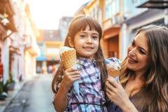 Mamã com a criança que come o gelado na rua da cidade Imagens de Stock Royalty Free