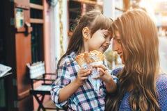 Mamã com a criança que come o gelado na rua da cidade Fotografia de Stock Royalty Free