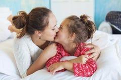 Mamã com a filha na cama Fotos de Stock