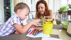 Mamã com o bebê do filho pintado com lápis coloridos vídeos de arquivo
