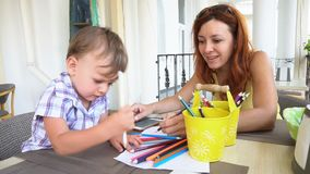 Mamã com o bebê do filho pintado com lápis coloridos video estoque