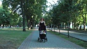 Mamã com o bebê, encontrando-se em um carrinho de criança em uma caminhada da noite Paisagem urbana vídeos de arquivo