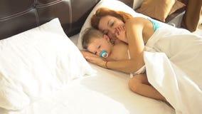 Mamã com o filho do bebê acordado na manhã no quarto filme