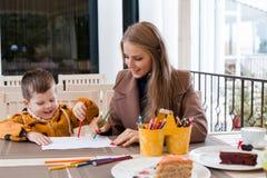 Mamã com os lápis coloridos tração do menino Foto de Stock