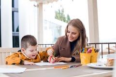 Mamã com os lápis coloridos tração do menino Imagens de Stock