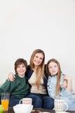 Mamã com seus dois filhos que bebem o suco no café da manhã Fotos de Stock Royalty Free