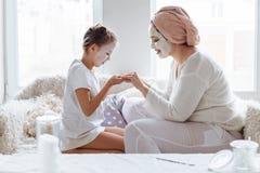 Mamã com sua filha que faz a máscara protetora da argila fotos de stock