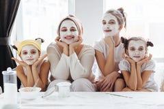 Mamã com suas filhas que fazem a máscara protetora da argila foto de stock