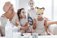 Mamã com suas filhas que fazem a máscara protetora da argila fotos de stock