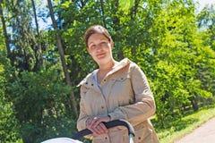 Mamã com um carrinho de criança no parque imagens de stock royalty free