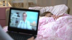 A mamã com uma filha doente pequena obtém a consulta de um doutor usando o bate-papo video em casa video estoque