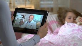 A mamã com uma filha doente pequena obtém a consulta de um doutor usando o bate-papo video em casa vídeos de arquivo