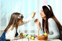 A mamã com uma menina é pintada em ovos da páscoa Fotografia de Stock