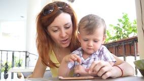 Mamã com uso do filho um smartphone para o Internet filme