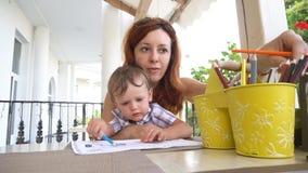 Mamã com uso do filho um smartphone para o Internet vídeos de arquivo