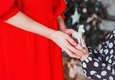 A mamã dá a sua filha um brinquedo Conceito do Natal Mãos da foto fotografia de stock royalty free