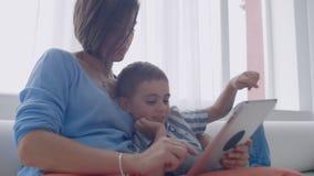 Mamã da família e filho felizes da criança que usa a tabuleta digital que senta-se no sofá, mãe de sorriso do pai com o filho da  video estoque