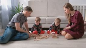 A mamã da família, o paizinho e dois irmãos gêmeos jogam junto a construção fora dos blocos de madeira no assoalho video estoque
