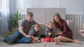 A mamã da família, o paizinho e dois irmãos gêmeos jogam junto a construção fora dos blocos de madeira no assoalho vídeos de arquivo