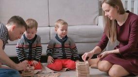 A mamã da família, o paizinho e dois irmãos gêmeos jogam junto a construção fora dos blocos de madeira no assoalho filme