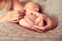 A mamã da mão mantém os pés desencapados do bebê, a mãe comunica wi Fotografia de Stock