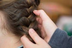 A mamã da menina faz um cabelo ou uma menina em um hairdresser_ fotografia de stock