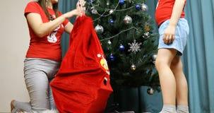 A mamã das ajudas do filho pôs os presentes de ano novo em um saco video estoque