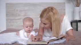A mamã de inquietação com livro lê a história do conto de fadas a seu bebê que a filha a beija então que se encontra na cama em c