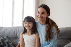 A mam? de sorriso com a filha pequena bonito senta-se na fala do sof? imagem de stock royalty free