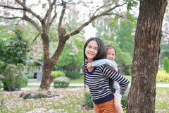 Mamã de sorriso que leva sua menina da criança pequena no jardim com inteiramente a flor do rosa da queda ao redor Família loving fotografia de stock